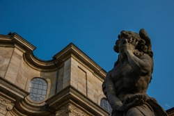 Detail of baroque statue with clear blue sky. Building facade background. Virtues and vices. Angel of a pathetic death. Sunset light relecting on the limestone masterpieces.