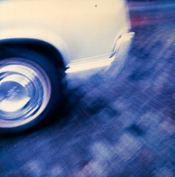 detail of white automobile wheel and body in motion on bluish background