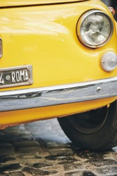 Detail view of an old Fiat 500 car typical of Italy in yellow color parked