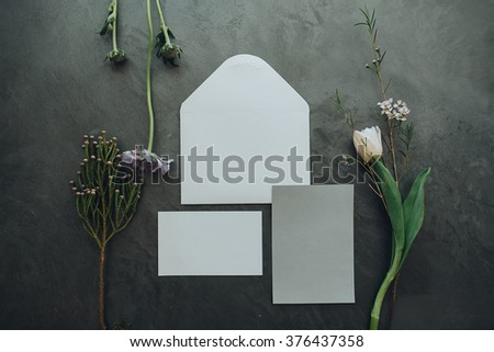 Details. Decor. On a gray textural background is white envelope for invitations, letterhead for the invitation, and nearby is a bouquet of dried flowers, tulips and purple wild flower