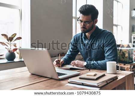 Developing new project. Thoughtful young man writing something down while working in the creative working space Stock photo ©