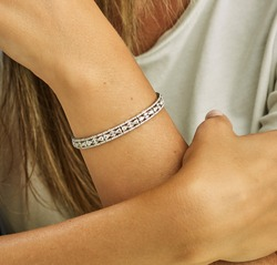 Diamond bracelet on young lady dressed in fashionable clothes