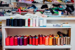 Different colorful thread spools for the weaving loom, Many different  thread spools colors in a sewing atelier.