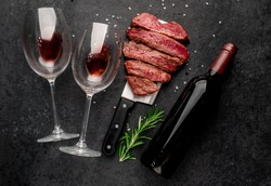 Different degrees of roasting beef steak in the shape of a heart with spices on a meat knife and bottles of red wine with glasses on a stone background. valentines day celebration concept