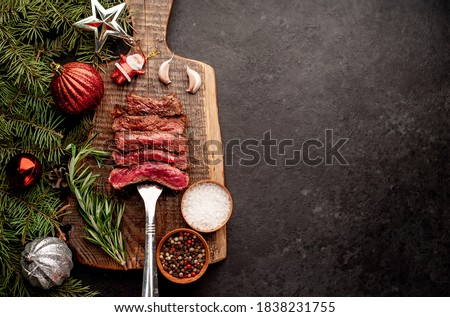 Different degrees of roasting of steak on a meat fork for Christmas on a background of a stone with a spruce and Christmas toys with copy space for your text