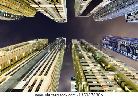 (different perspective) Stunning view from the bottom to the top of some high skyscrapers and towers illuminated during the night in Dubai Marina. Dubai, United Arab Emirates. #1359878306