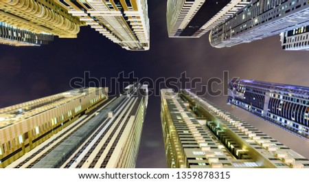 (different perspective) Stunning view from the bottom to the top of some high skyscrapers and towers illuminated during the night in Dubai Marina. Dubai, United Arab Emirates. #1359878315