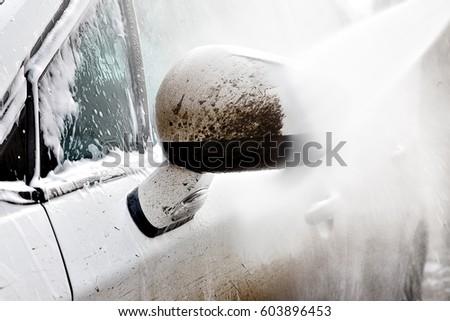 Dirty car wash high pressure water. Car shampoo, foam, no contact car wash. White car.