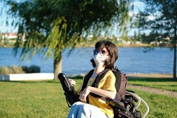 Disabled woman with muscular dystrophy in an electric wheelchair wearing a white face mask for protection during coronavirus outbreak