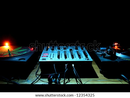 2 DJ turntables and electronic mixer in darkness