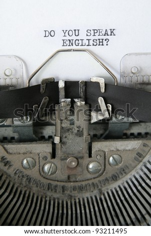 'do you speak English' written on an old typewriter, detail vertical photo.