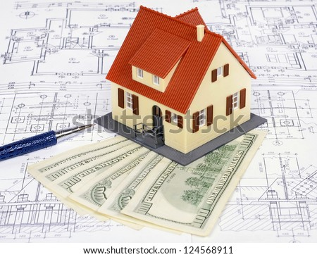 dollar banknotes and a model house on a construction plan for house building; concept of buying a house