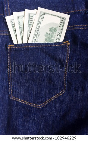 100-dollar bills in the pocket of blue jeans