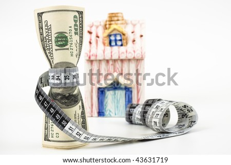 100 dollar bills tight with a measuring tape a small house in the background white background
