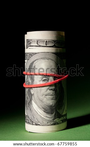 100 Dollar roll tightened with red rubber band. Sad Franklin looks at you. Green black background. Shade hides a zero.