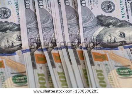 100 Dollars bill and portrait Benjamin Franklin on USA money banknote. Close up of one hundred dollar bills on table.