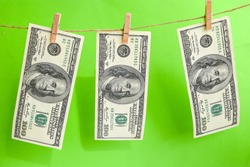 100 dollars on a rope, dollars with a clothespin on a rope isolated on a green background, Concept - money laundering. Dollars are dried on the ropes. Dollars after washing. Money earned honestly