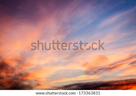 Dramatic sunset sky with orange colored clouds.