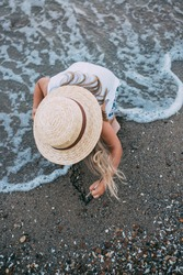 Draw in the sand. A little girl in a straw hat sits on the seashore, draws on the sand with a feather, her blonde hair flutters in the wind. The girl draws on the sand.