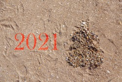 2021: drawing of a Christmas tree made of shells on the sand. copy space. New year on the beach