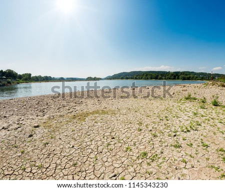 \nDried-out riverbed with stones and sediments in the river Rhine with low water level between groins on a sunny day, caused by prolonged drought, North Rhine-Westphalia, Germany, Europe