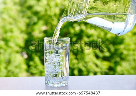 drinking water is poured from a jug into a glass on a green nature outdoors background .