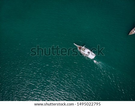 Drone view of the two light boats sailing the turquoise sea, leaving a beautiful trace on the water; relaxation and peace; tranquility concept.