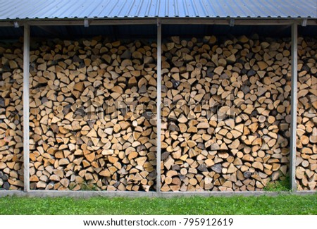dry chopped firewood logs in a pile prepared for winter season