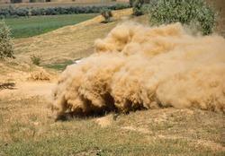 dust raised by a car on a dirt road. blur