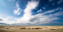 East Frisian Island: Wonderful dune beach on the North Sea island Langeoog in Germany with blue sky and clouds on a beautiful and windy summer day; very healthy and quiet environment in Europe
