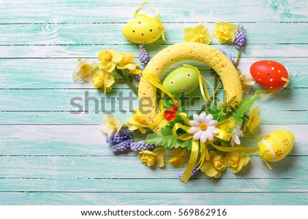Easter background for design. Decorative Easter wreath and eggs,   bright spring flowers on turquoise wooden background.Selective focus. Place for text.  #569862916