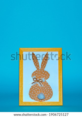 Easter bunny paper applique in yellow photo frame on blue background. Happy Easter Day concept. Minimalizm. Easter card. Copyspace for text.                                           Stok fotoğraf ©