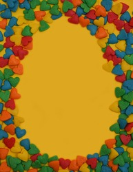 Easter Egg form from colorful heart shape sweet candy on bright yellow background.  Happy Easter Day card concept. Copy space for text. Minimal concept.