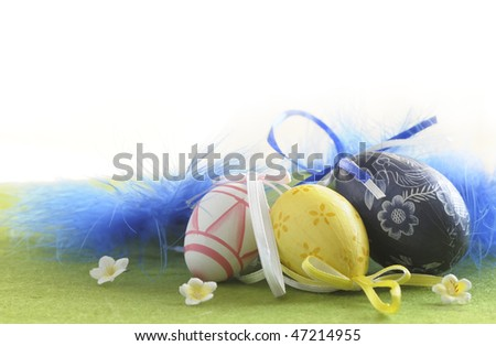 Easter Eggs sitting on grass field with blue feather background - stock photo