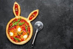 Easter pizza in the form of a hare with eggs on a stone background with copy space for your text