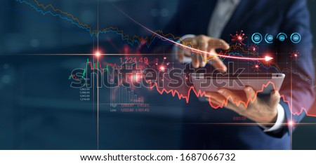 Economic crisis, Businessman using tablet analyzing sales data and economic graph chart that is falling due to the corona virus crisis, Covid-19, stock market crash caused.