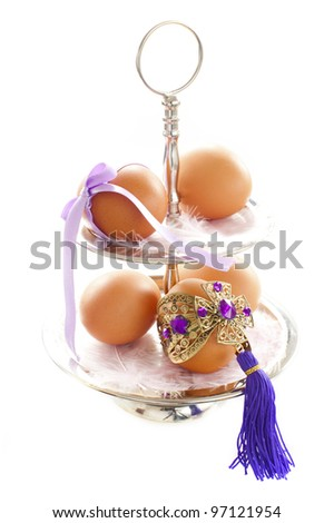 5 eggs at the cakestand, decorated with ribbon and decorations on a white background