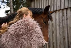 Eine Frau Anfang 40, füttert ihr Pferd mit den Möhren, sie hat einen Korb an der Hand, der Kopftuch, eine Decke über die Schulter. Es ist April, der Stahl ist aus dem Holz. Frau kuschelt mit Pferd