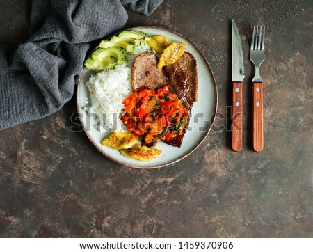 El Bistec a la Criolla  -  colombian dish traditional - beef steak with tomatoes sauce, rice, avocado, bananas fries                                    Foto stock ©