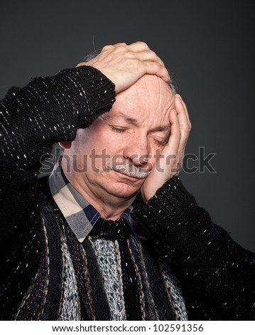 Elderly man suffering from a headache and toothache