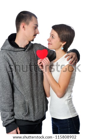 embracing happy young adult couple with red heart on white background