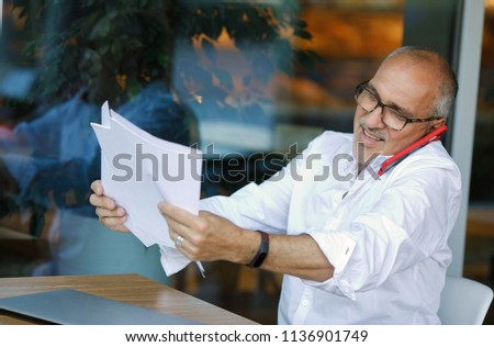 ad4d6d193c09 Emotional portrait of a positive and happy mature business man in a white  shirt and glasses