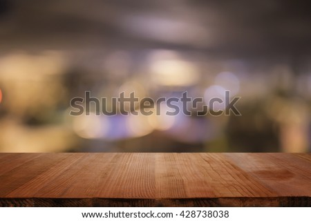 Empty brown wooden table and blur background of abstract  of resturant lights people enjoy eating ,can be used for montage or display your products   #428738038