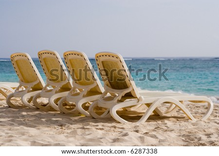 4 empty loungers on a tropical beach (Punta Cana, Dominican Republic)