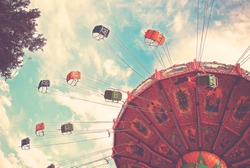 empty swing ride going around at a fair toned with a retro vintage instagram filter