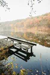 Empty wooden mole in the water of the lake. Old fishing wharf for hired boats and swimmers. Fall landscape in retro tones. The trees are reflected in the water