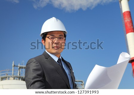 engineer oil refinery checking plan on location site with tower and blue sky background