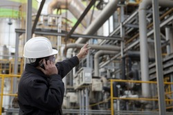 engineer pointing against pipeline inside large oil refinery