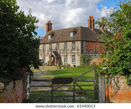 English Rural Manor Farmhouse and garden viewed from a five bar gate
