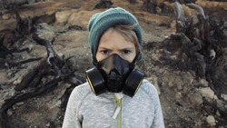 Environmental pollution, ecological disaster, nuclear war, post apocalypse concept. Care for future generations. Child in protective mask, face-guard to prevent breathing toxic air. Covid-19, Coronav